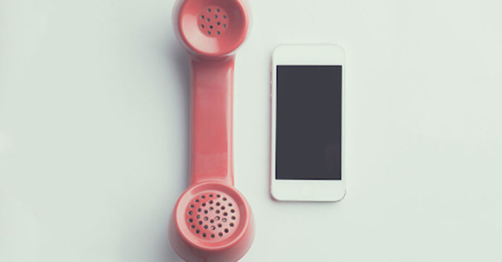 pink rotary phone next to smartphone